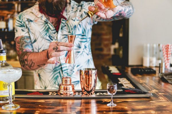 A bartender demonstrates the proper use of a cocktail jigger.