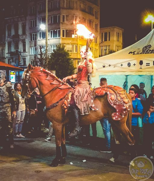 A woman carrying a torch rides a horse at Zwanze Day 2017