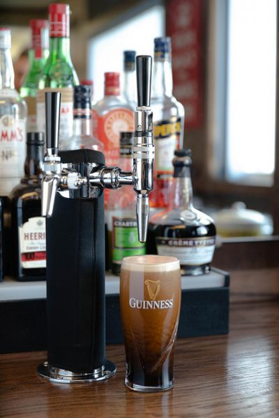 A freshly poured Guinness beer sits under a stout beer faucet.
