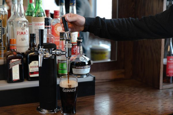 Top off your pint by pushing the tap handle from you. This limits the power of the flow. The beer should be set straight under the spout during this second pour.