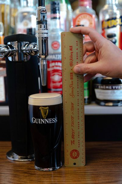 """The amount of foamy head from the tried-and-true, proper way to pour a Guinness, measured in at 11/16"""" exactly."""